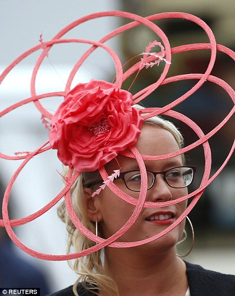 A racing fan made an impression in a striking coral hat with a large flower corsage at its centre