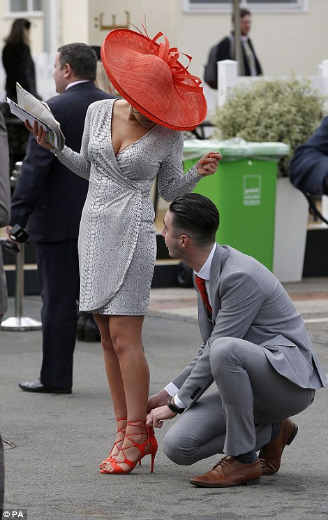 A woman had to call on her male companion for some help in adjusting her red strappy sandals