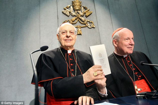 Cardinal Lorenzo Baldisseri and Cardinal Christoph Schonborn hold up a copy of Pope Francis' 'The Joy of Love' at the Holy See Press Office today