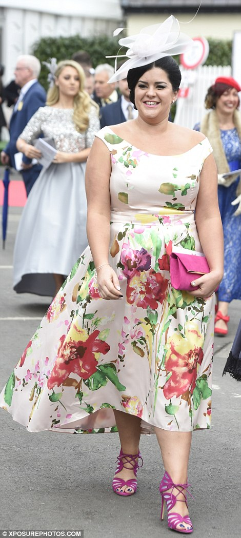 A woman in a floral dress with magenta accessories