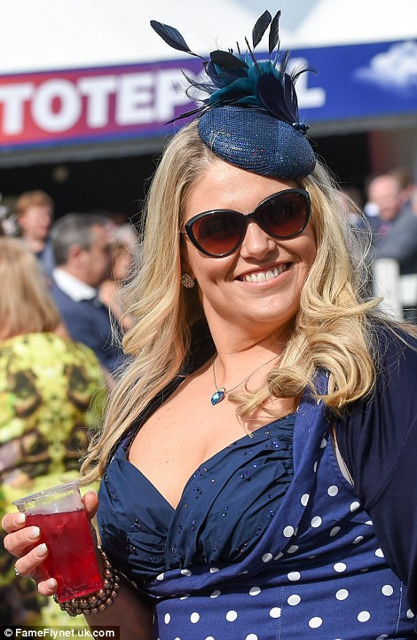 A woman in a navy polka dot dress grins for the camera at Aintree