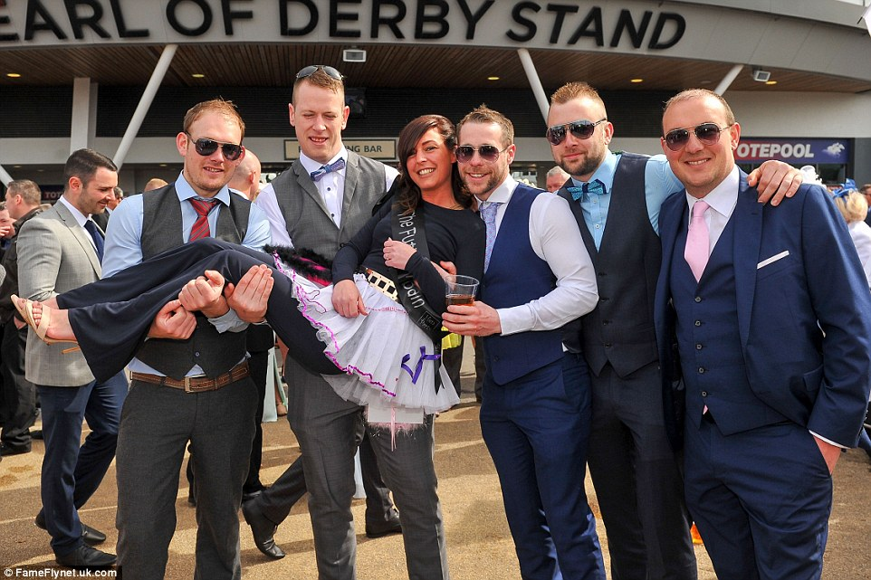 A woman celebrating her hen party cot a lift from some male racing fans outside the Earl of Derby stand