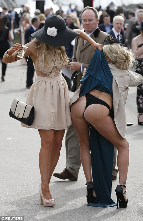 In outrageous scenes a woman allowed her friend to pull up her skirt to reveal her black thong underneath