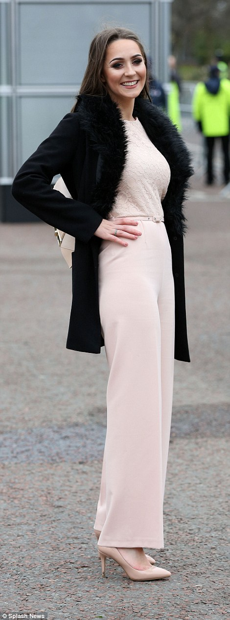 A woman cut an elegant figure in a pale pink jumpsuit and a black fur trimmed coat