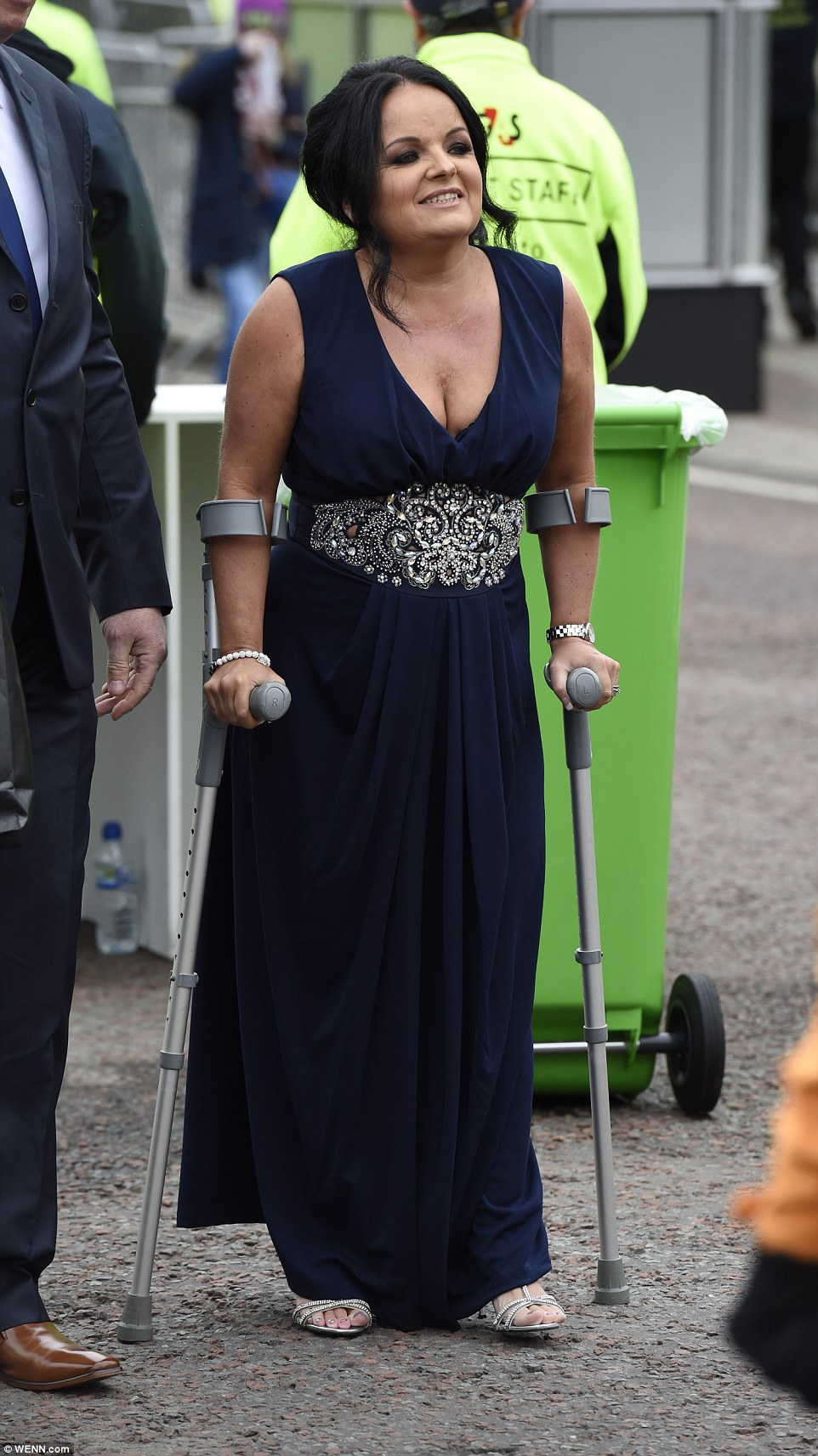One woman didn't let being on crutches hinder her glamour as she stepped out in silver high heeled sandals and an navy dress with an embellished panel at the middle