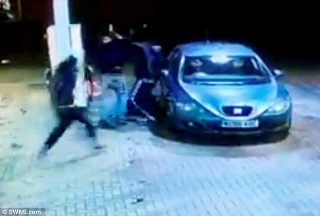 Cornered: In the video the victim desperately tries to run away from his attackers only to stumble and fall against a car which had just been filled up at a garage forecourt in the early hours of the morning