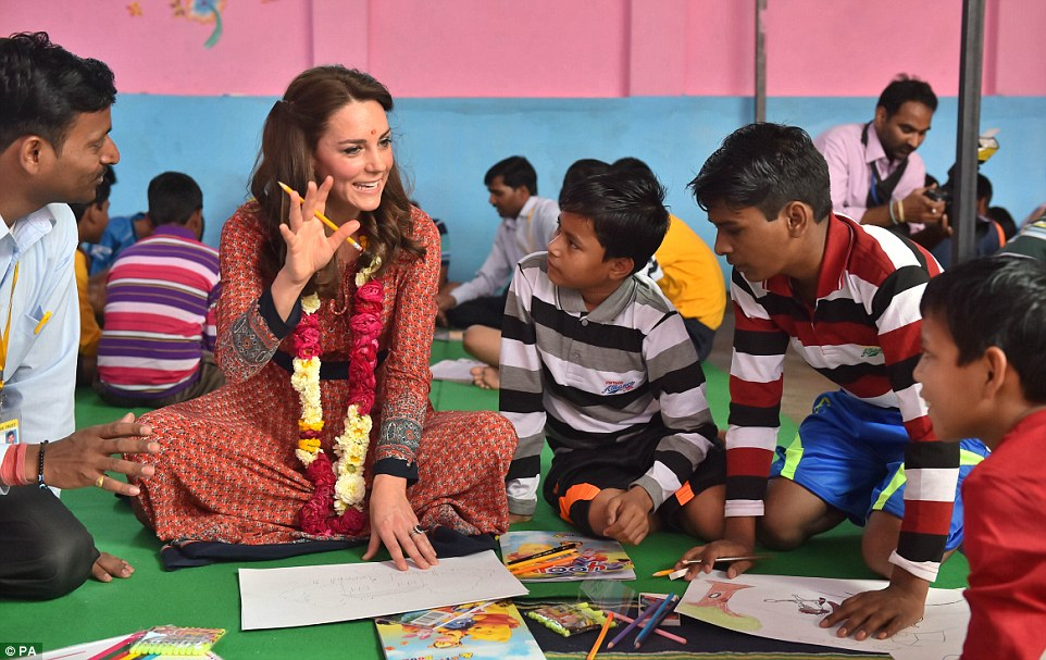Art class: The Duchess of Cambridge sat cross-legged as she drew pictures with some of the street children helped by the charity