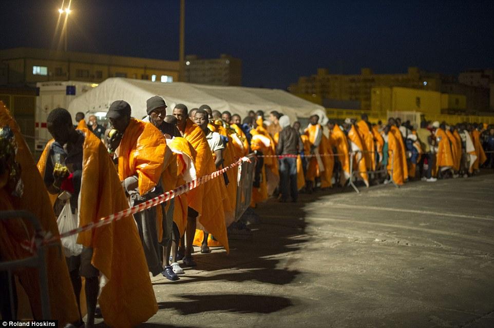 Esperando: Las colas de los recién llegados a la espera de ser procesada serpenteado alrededor del puerto de Palermo, después de que el barco noruego aterrizaron ayer por la noche