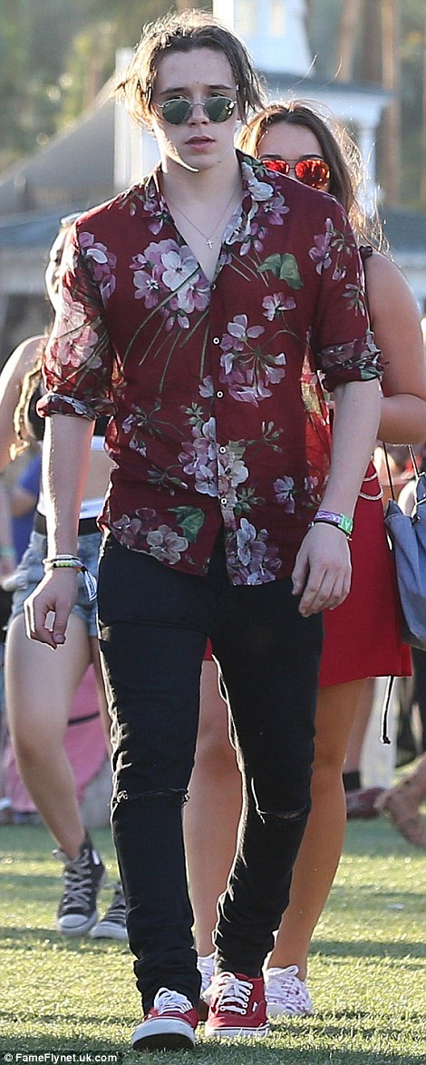 Bold: Brooklyn Beckham added a tropical touch to his Coachella look by rocking a patterned button-up shirt with his dark trousers
