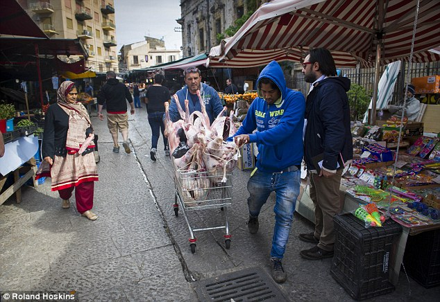 Central: Street vendors sell pigs' heads and gut fish while Mafiosos collect protection money at Balleró street market in the centre of the city
