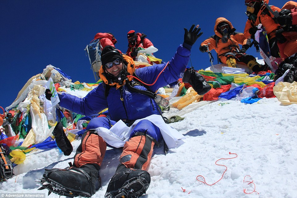 Gavin is pictured on the summit of Everest, surrounded by other successful climbers andTibetan prayer flags