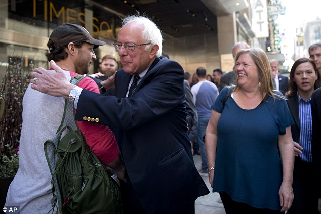 Sanders hugs a pedestrian as he takes a walk in New York's Times Square this morning