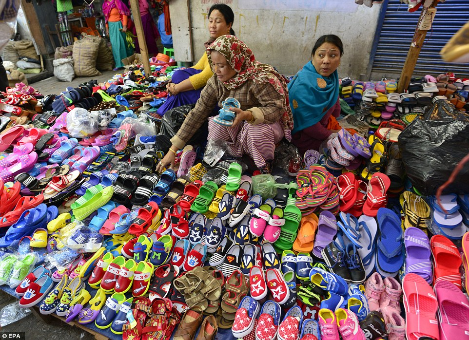 Run exclusively by women, it is reportedly the largest all-women market in Asia and possibly the world.  Three women sell flipflops and colourful shoes (pictured)