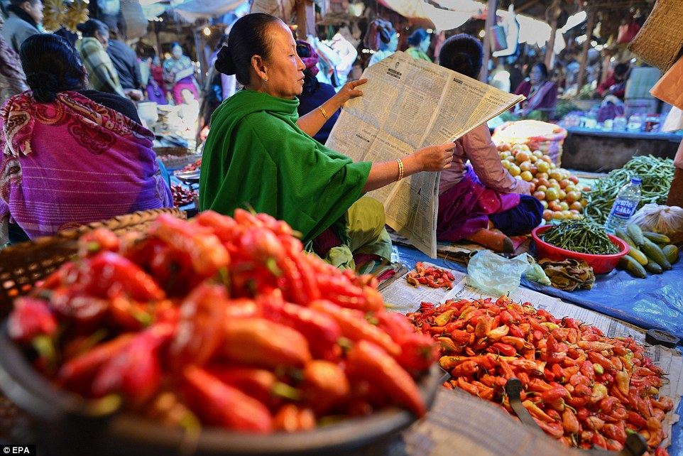 Although Ima Keithel was damaged in the 4 January earthquake, it has returned back to normal. Nine deaths were reported from in and around Imphal due to falling debris. Imphal has a population of some 270,000 and people were jolted from their sleep and ran out of their homes in panic when the earth shook. A woman reads the news at her vegetable stall (pictured)