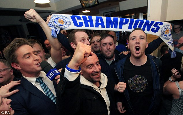 Leicester City fans celebrate in the Market Tavern in Leicester after seeing their side crowned Barclays Premier League champions following Tottenham Hotspur's 2-2 drew against Chelsea earlier this evening