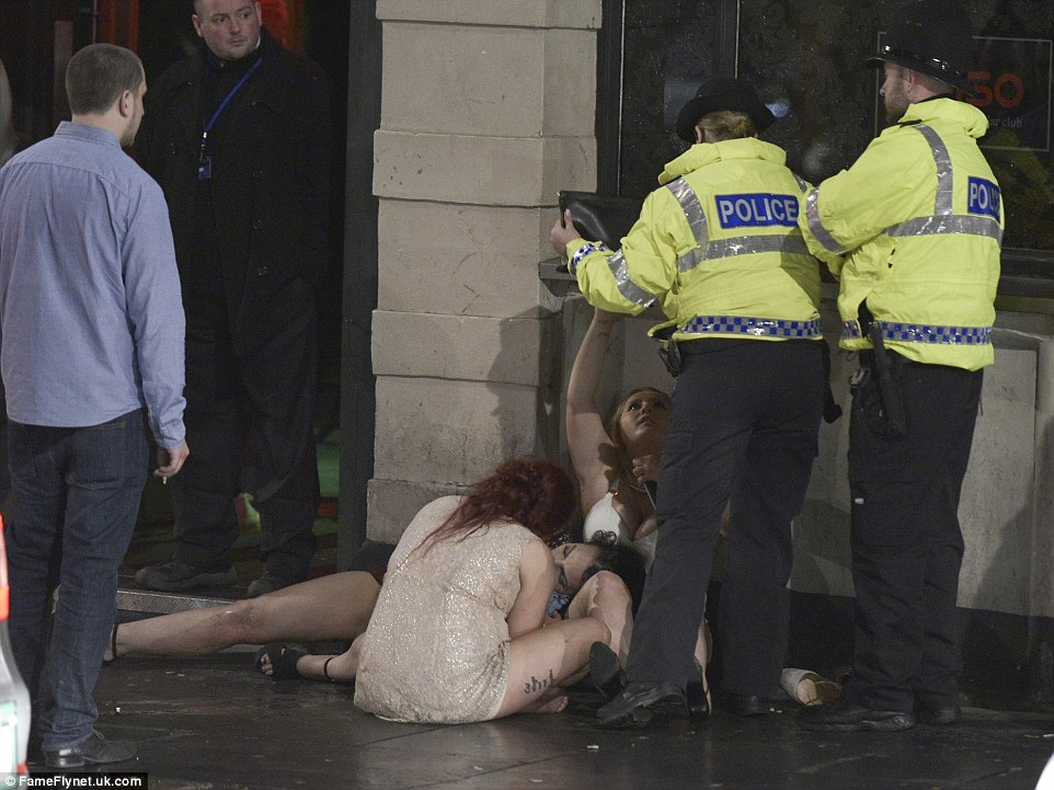 Two police officers help a young woman and her friends as one sprawls out on the pavement following a night out in the party capital