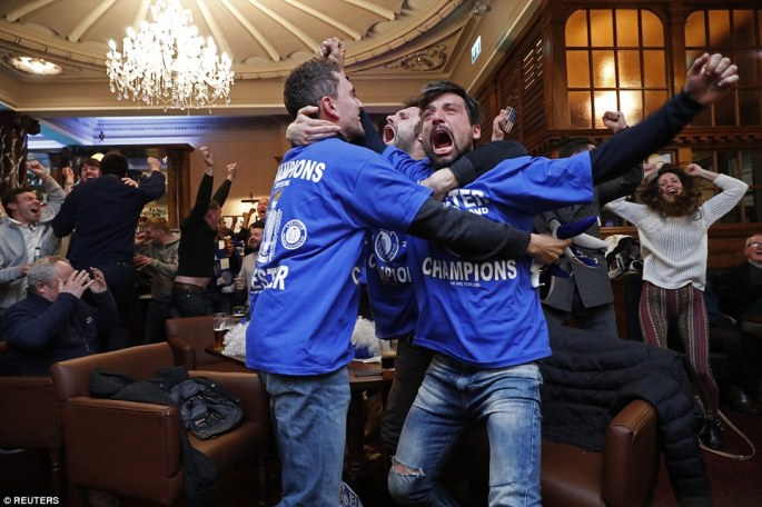 Leicester City fans celebrate at the final whistle of the Chelsea v Spurs match, as their team are crowned champions of England