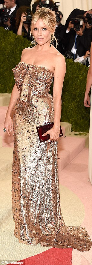 British beauty: Sienna Miller stunned in a gold strapless gown with ruby embellishments and matching red clutch