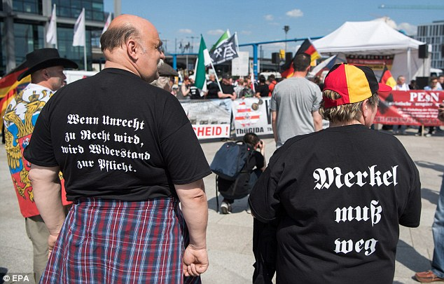 Protesters wear t-shirts written with the messages 'When wrong becomes right, resistance becomes obligatory' and 'Merkel must go'