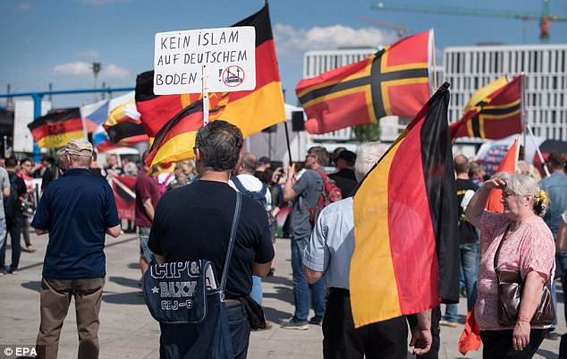 Participants in a march of right-wing groups demonstrate in front of the central train station with a sign written with 'No Islam on German soil'