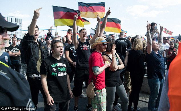 Right-wing protesters take part in a rally against German Chancellor Angela Merkel's migration policies in Berlin earlier today