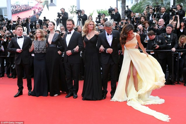 Oh dear: Amal Clooney found herself struggling with the flowing train of her gorgeous gown as she attended the premiere of her husband's new film Money Monster at the 69th annual Cannes Film Festival