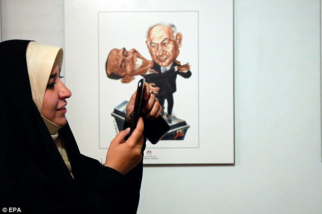 PM Benjamin Netanyahu said Sunday it was more than Iran's belligerent policies that Israel opposed, but its values. Pictured: A woman inspects her pictures from the exhibition
