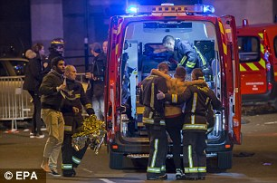 Wounded people are helped by the emergency services after explosions outside the Stade de France in Paris, France last year