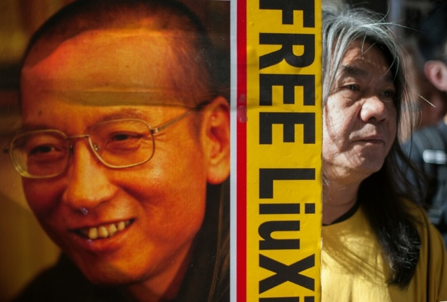 "Hong Kong activist and legislator Leung Kwok-hung (R), popularly known as ""Long Hair"", holds a placard calling for the release of Chinese human rights activi..."