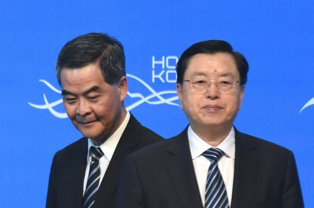 Hong Kong Chief Executive Leung Chun-ying (L) walks past Zhang Dejiang (R), who chairs China's communist-controlled legislature, as they open the Belt and Ro...