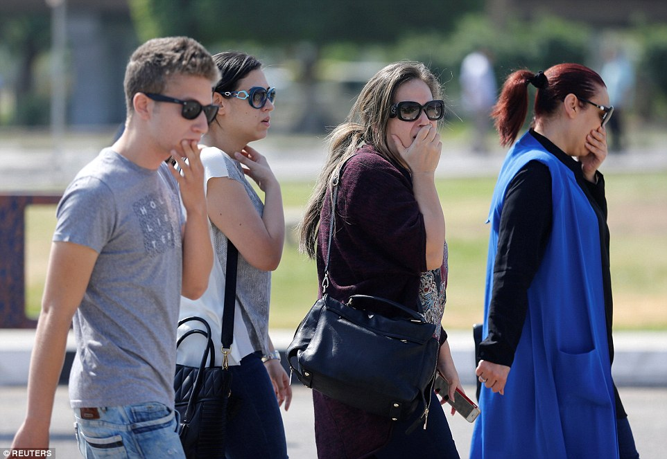 Relatives and friends of passengers flying on the EgyptAir react as they wait outside the Egyptair in-flight service building at Cairo Airport