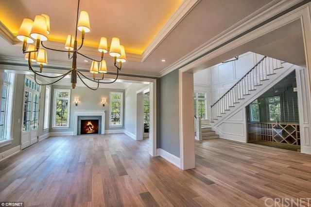 Nice look: The living room has a working fire place with wall sconces and French windows