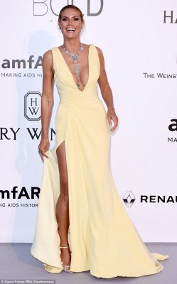Beauty: The supermodel, 42, showed off her chest and legs in a plunging yellow floor-length number with thigh-high split