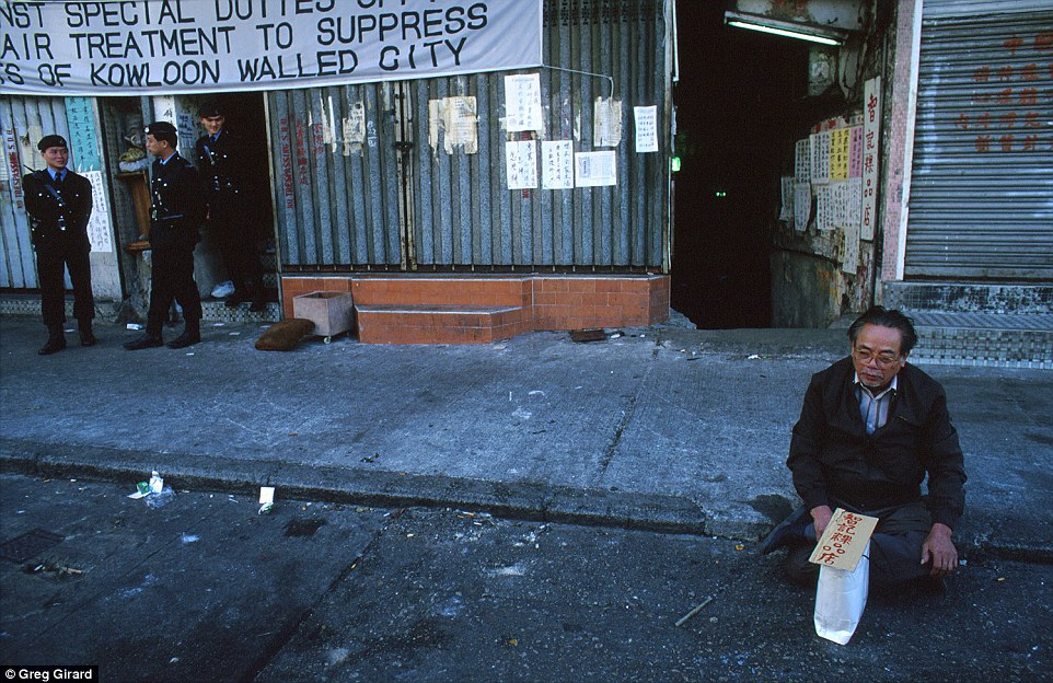 A resident upset with compensation protests on the pavement in front of Walled City during clearance operation by police