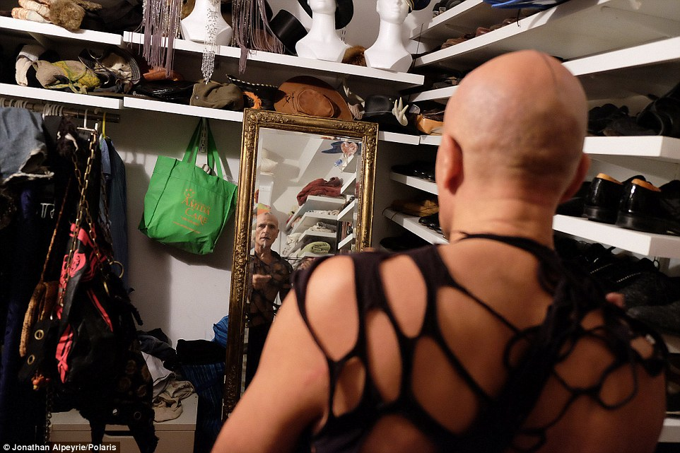 King of the castle: The real estate mogul looks into the mirror as he tries on an outfit before an open sexuality party