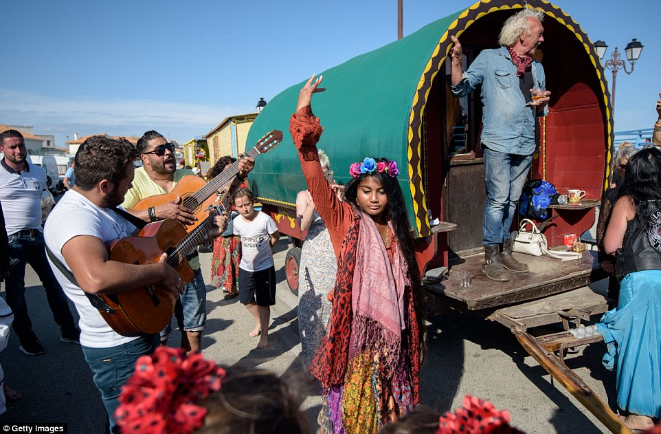 Gypsies play guitar and dance in front of their folklore wagon on May 24, 2016 during the procession down to the French shoreline