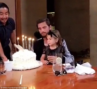 Birthday boy: The family gathered in a private dining room where Scott, with daughter Penelope on his lap, was presented with his birthday cake covered in white frosting with several lit white candles and a white heart