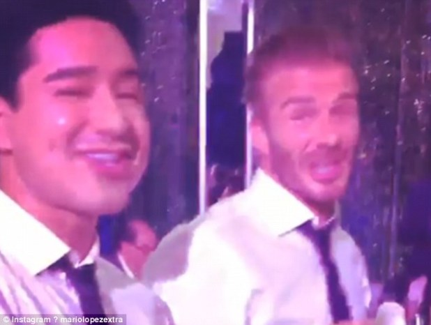 Dancing queen: Her husband David Beckham (right), along with Mario Lopez (left), were filmed letting their hair down