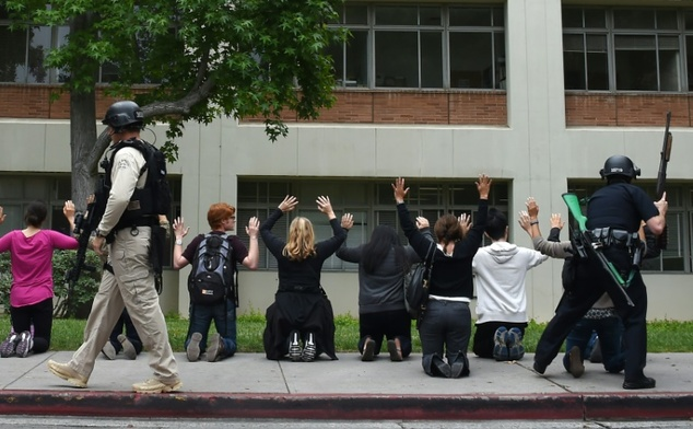 Many students and staff at the University of California's Los Angeles campus (UCLA) could be seen walking out of buildings with their arms raised while other...