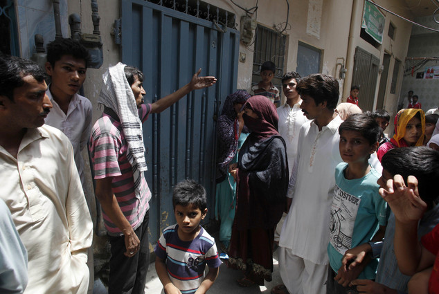 Local residents gather outside the home of Parveen Rafiq, who has confessed to killing her daughter for refusing to have a traditional wedding