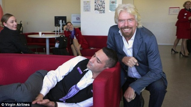 Virgin founder Richard Branson is photographed grinning next to a sleeping employee in the Sydney office