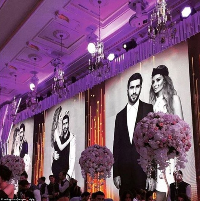 In love: The venue was also decorated with huge pictures of the couple on their official wedding shoot (above)