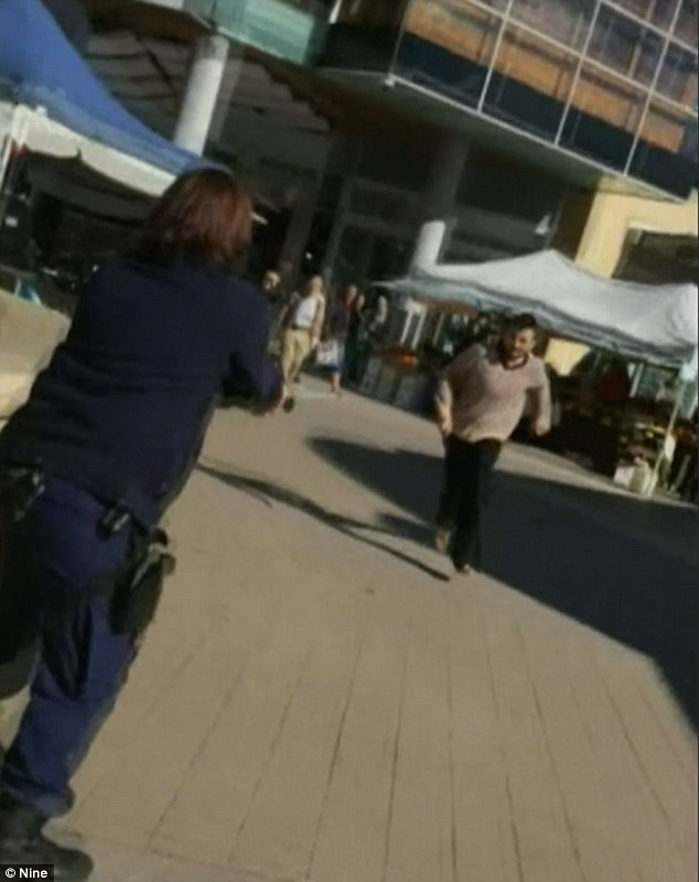 A man carrying a carving knife, 23, was shot by police at Westfield shopping centre in Hornsby, north-west Sydney after appearing to lunge at police (pictured)