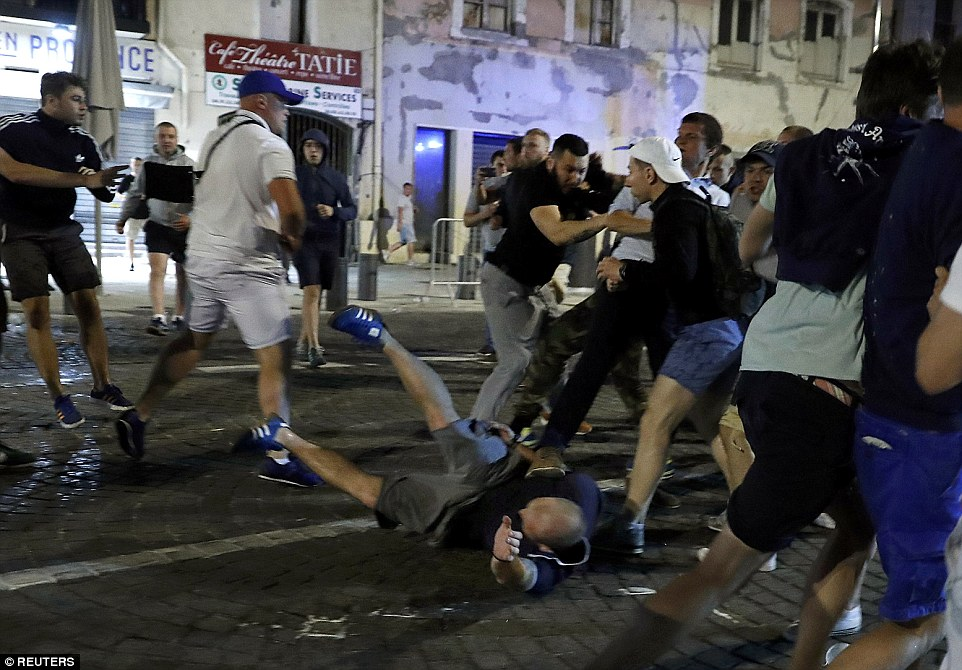 An English supporter is bundled to the floor as local youths and football fans battle it out on the streets of Marseille this evening
