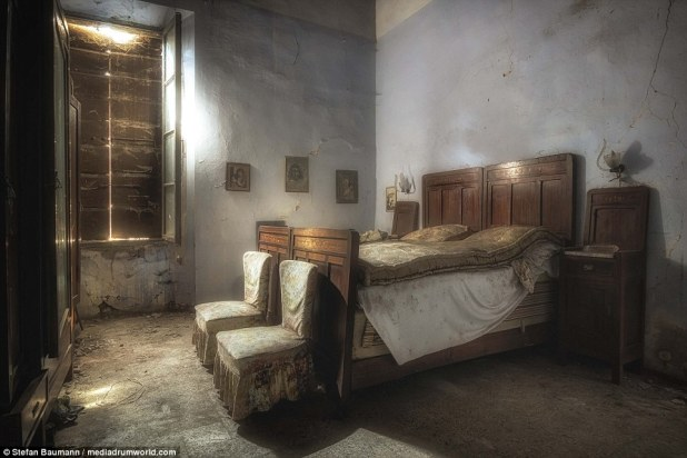 The master bedroom in an abandoned Castello in Italy has photographs of the owner's grandchildren hanging on the wall