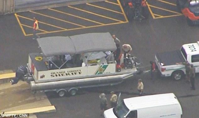 El cuerpo del niño es conducido lejos del lago en la parte trasera del vehículo de un departamento de Sheriff del Condado de Orange
