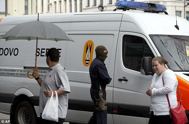 Belgians walk past a bomb squad van outside the central station in Antwerp. Police and the bomb squad unit responded to a suspect package in the station as the country was put on heightened alert