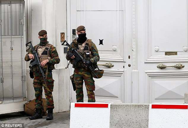 Belgian soldiers, their faces covered, stand guard outside the prime minister's office today