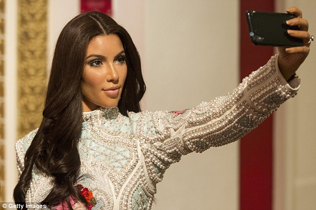 How do I look? Kim Kardashian West, 35, is so well known for taking selfies that even her waxwork at Madame Tussauds in London has her posed with her camera phone in hand - at a flattering angle of course