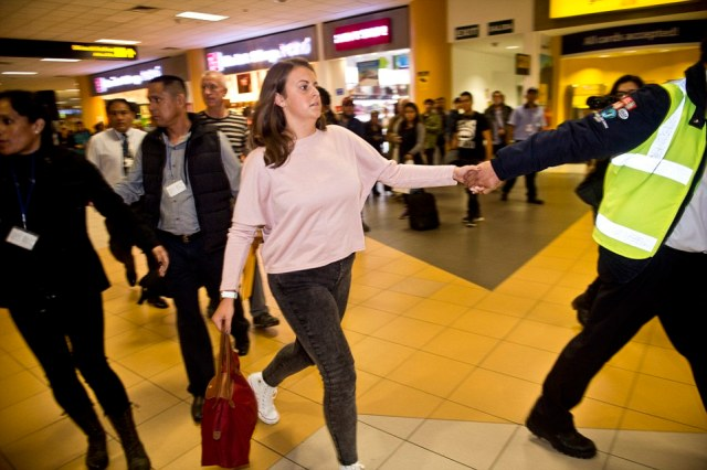Reid was surrounded by a handful of Peruvian officials as she was pulled by the hand through the airport ahead of her flight home